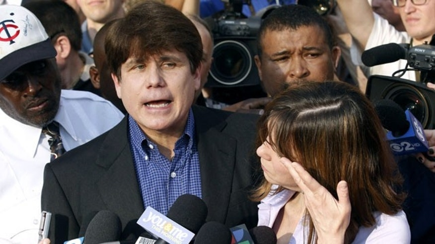 In this March 14, 2012 file photo, former Illinois Gov. Rod Blagojevich speaks to the media outside his home in Chicago, as his wife Patti wipes away her tears a day before he was to report to a prison in Littleton,. Colo., to begin a 14-year prison sentence on corruption charges. (AP Photo/M. Spencer Green, File