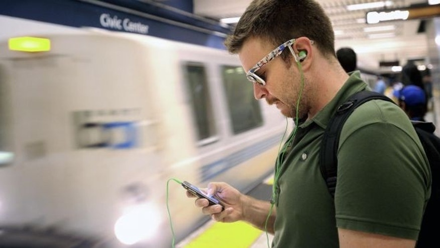 Aug. 13, 2011: In this file photo, Nick Sabatasso checks his cell phone while waiting for a BART train at San Francisco's Civic Center station.