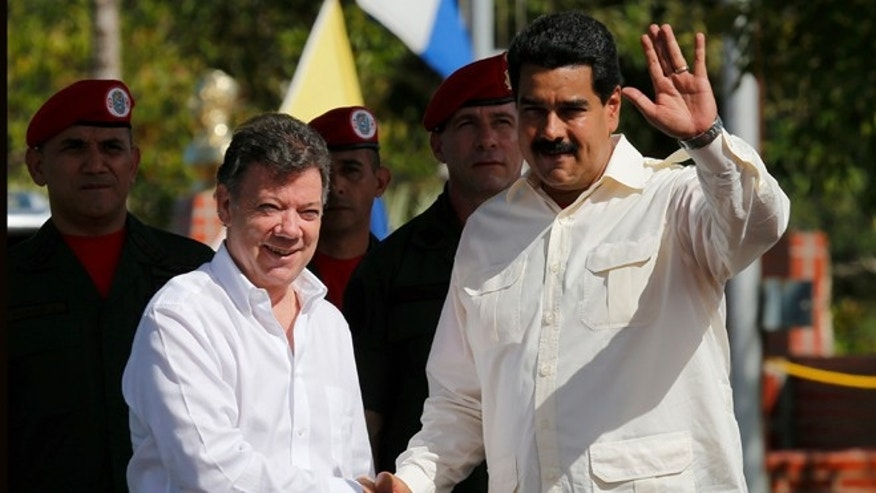 Venezuela's President Nicolas Maduro, right, waves as he shakes hands with Colombia's President Juan Manuel Santos prior a meeting in Puerto Ayacucho, Venezuela, Monday, July 22, 2013. (AP Photo/Fernando Llano)