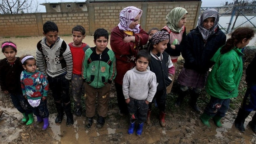 Syrian refugees pose for a photograph after their tents flooded from the rain, at a temporary refugee camp, in the eastern Lebanese town of Al-Faour near the border with Syria.