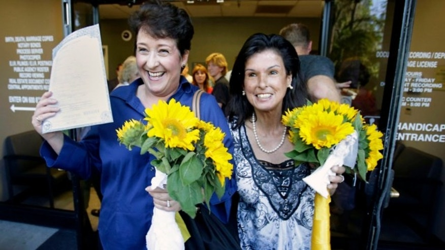 June 28, 2013: Nicola Simmersbach, left, displays a marriage license as she Diana Luiz, leaves the Sacramento County Recorder's office after they got married in Sacramento, Calif.