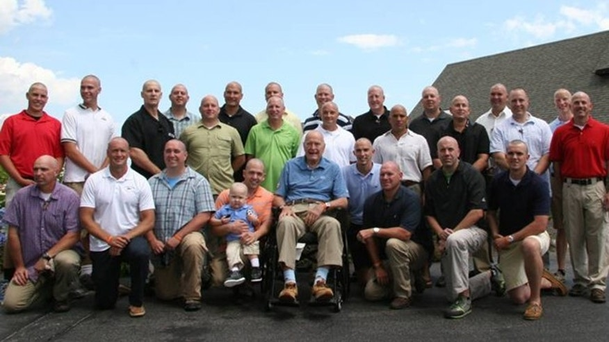 Members of George H.W. Bush's security detail pose for a picture after shaving their heads in solidarity with a young cancer patient.