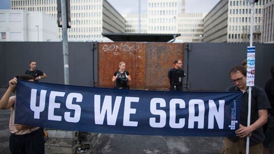 July 29, 2013: Demonstrators hold a banner during a protest against the U.S. National Security Agency, NSA, and the German intelligence agency, BND, during a rally in Berlin.