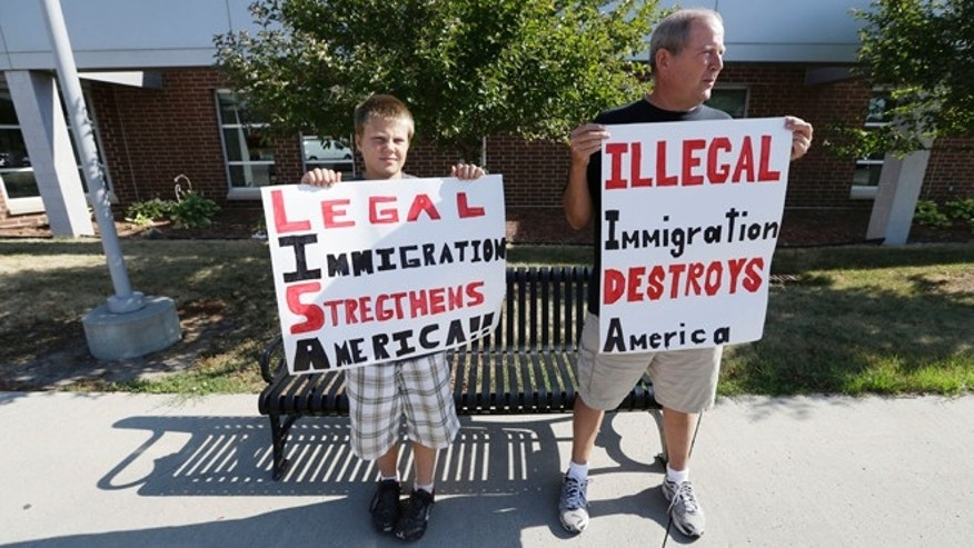 FILE: Aug. 2, 2013: Larry DeRocher, of Onawa, Iowa, right, and grandson Blake outside a forum on immigration held by Democratic Sens. Tom Harkin, Iowa, and Dick Durbin, Ill., in Ames, Iowa.