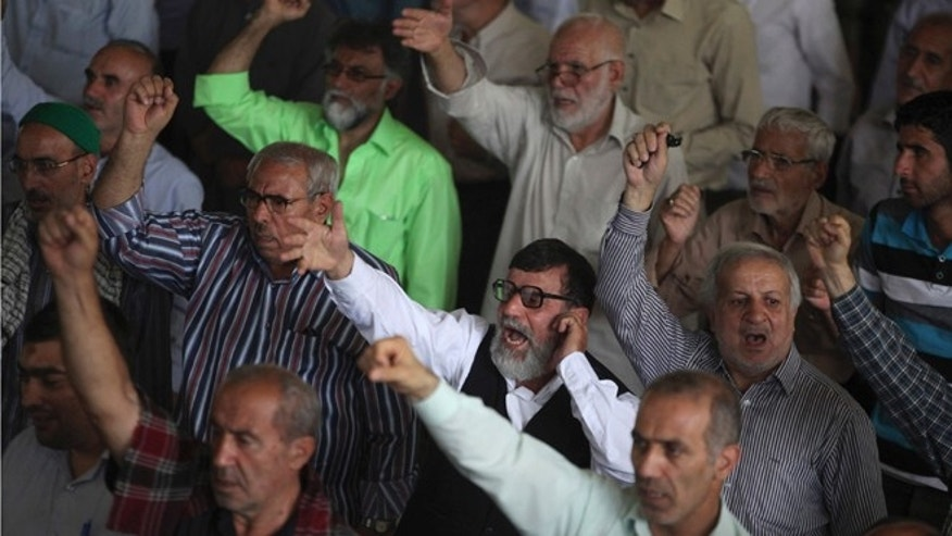 FILE: July 26, 2013: Iranian worshippers during Friday prayers for the Muslim holy fasting month of Ramadan, at the Tehran University campus in Tehran, Iran.