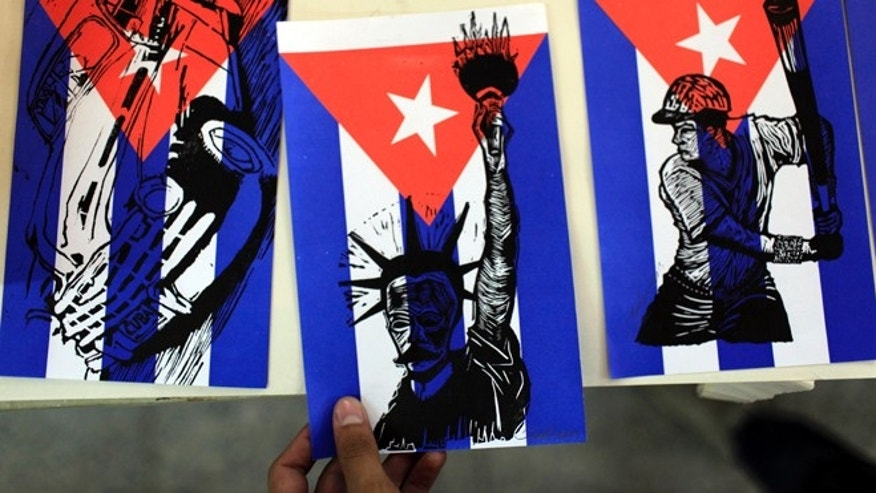 In this July 8, 2013 photo, a man takes a paper Cuban flag covered by an image of the Statue of Liberty and the face of the Cuban hero Jose Marti at the Experimental Graphic Workshop in Havana, Cuba. For a place where most people earn just $20 a month at their government jobs, Havana can be a surprisingly expensive place to be a traveler. But there are plenty of free ways to have fun in this city known for sea, sun and salsa. (AP Photo/Franklin Reyes)