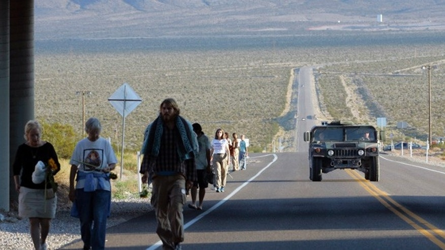 A U.S. Air Force humvee is driven past as anti-nuclear activists walk after a sunrise ceremony just outside the Nevada test site near Mercury, Nevada, 60 miles north of Las Vegas.