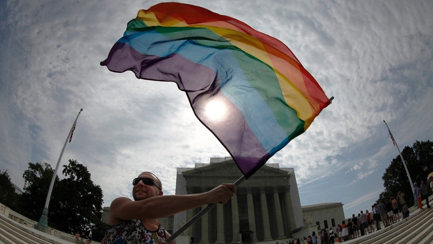 Gay marriage supporter Vin Testa waves a rainbow flag in anticipation of U.S. Supreme Court rulings in the cases against California's gay marriage ban known as Prop 8 and the 1996 federal Defense of Marriage Act (DOMA), outside the court building in Washington, June 24, 2013. The court did not release its rulings on either case Monday. Picture taken with fish-eye lens. REUTERS/Jonathan Ernst    (UNITED STATES - Tags: POLITICS CRIME LAW) - RTX10ZCW