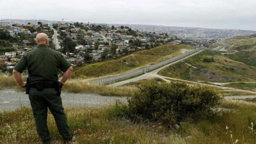 April 13, 2011: United States border patrol agent Shawn Gisler looks across the fence at Mexico as he patrols the U.S. border in San Ysidro, California.
