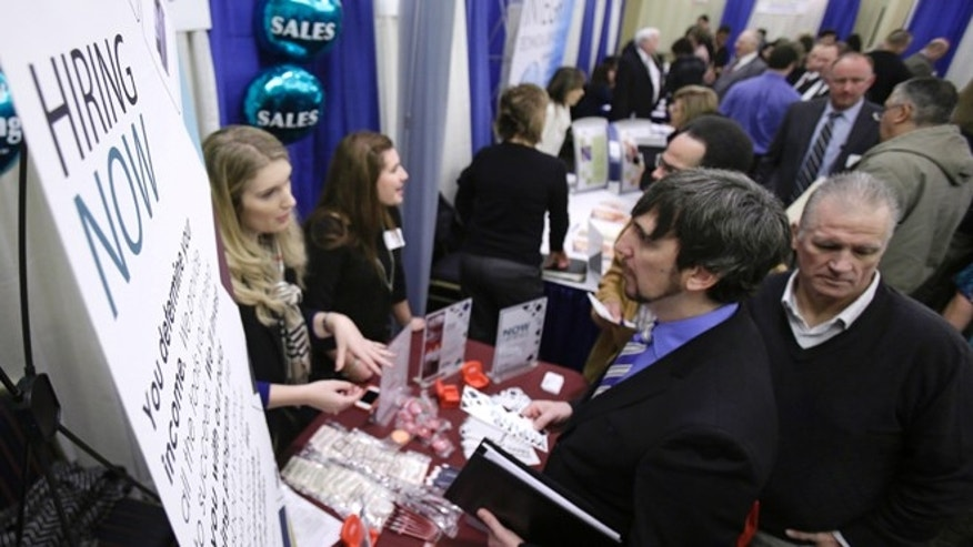 FILE: Jan. 16, 2013: Job seekers talk with employers during a job fair in Cuyahoga Falls, Ohio.