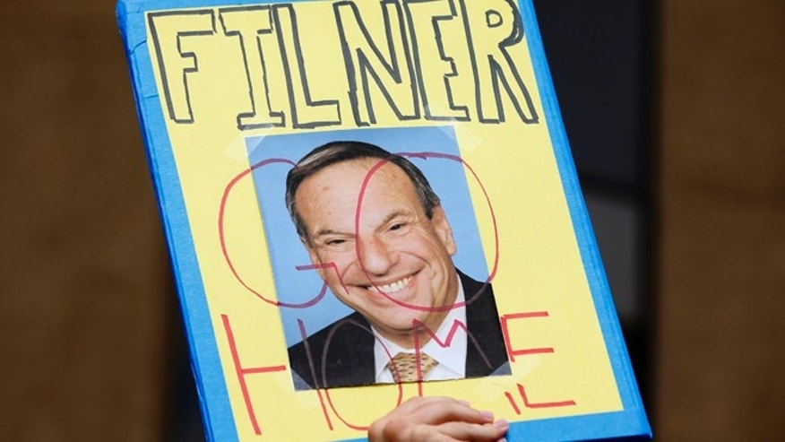 FILE: August 18, 2013: A demonstrator holds up a sign to protest San Diego Mayor Bob Filner refusing to resign over sexual harassment accusations, during a rally and march in downtown San Diego, Calif.