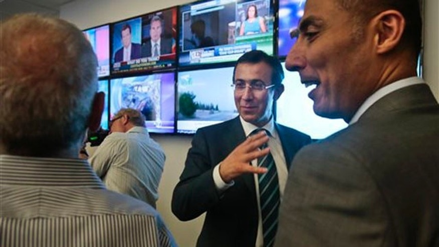 Aug. 20, 2013: Ehab Al Shihabi, second from right, interim CEO for Al-Jazeera America, gestures as he chats with newsroom staff after the network's first broadcast.