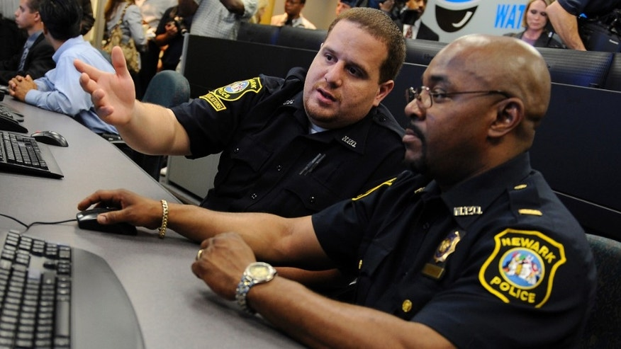NEWARK, NJ - JULY 1:  Communications clerk Angel Castro (L) demonstrates the movements of a remote surveillance camera to Lt. Darryl Martin in the newly-opened Surveillance Operations Center of the Newark, New Jersey Police Department before a press conference in Newark, July 1, 2008. (Photo by Jeff Zelevansky/Getty Images)