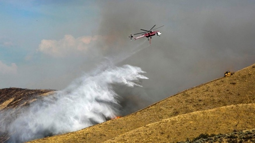 Aug 20, 2013: A fire attack helicopter drops water along a draw northeast of Hilltop Cafe on Idaho 21 as a bulldozer plows a fire line on the ridge northeast of Boise.
