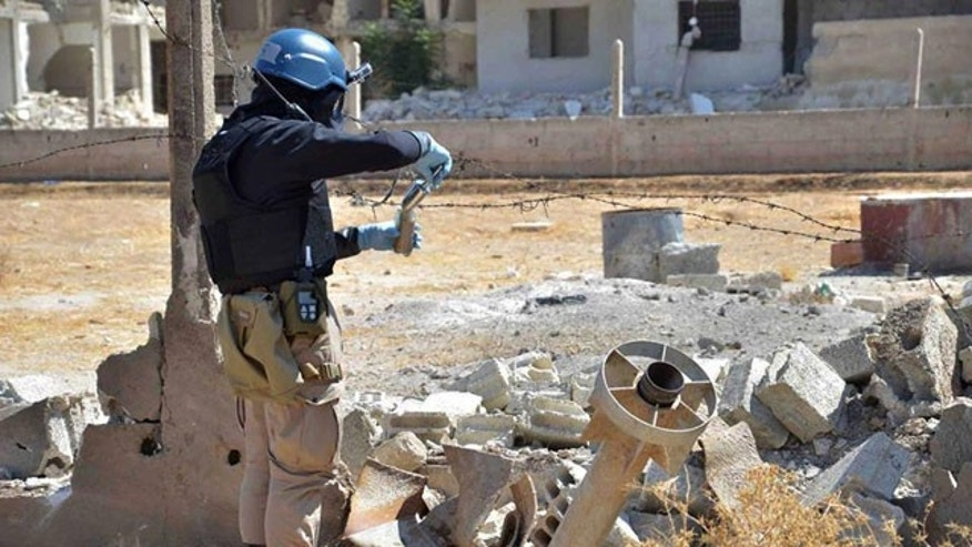 August 28, 2013: In this citizen journalism image provided by the United media office of Arbeen which has been authenticated based on its contents and other AP reporting, a member of a UN investigation team takes samples of sands near a part of a missile is likely to be one of the chemical rockets according to activists, in the Damascus countryside of Ain Terma, Syria. (AP Photo/United Media Office of Arbeen, File)
