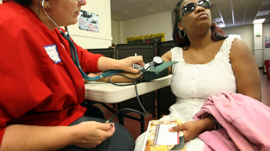 LOS ANGELES, CA - JULY 10:  Nurse Allison Miller (L) checks the blood pressure of Keri Anderson as nurses and physicians give free basic health screenings and call attention to what they say is the ongoing healthcare emergency despite the decision of the U.S. Supreme Court to uphold the Affordable Care Act, on July 10, 2012 in Los Angeles, California. Three days of free screenings in the Los Angeles area are part of the Medicare for All tour which is making up to two dozen stops across California between June 19 and July 12. The California Nurses Association says that 30 percent of Los Angeles County adults are uninsured and 18 percent cannot afford doctor visits.   (Photo by David McNew/Getty Images)