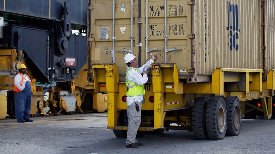 Longshoremen work on unloading a container ship at Port Everglades.