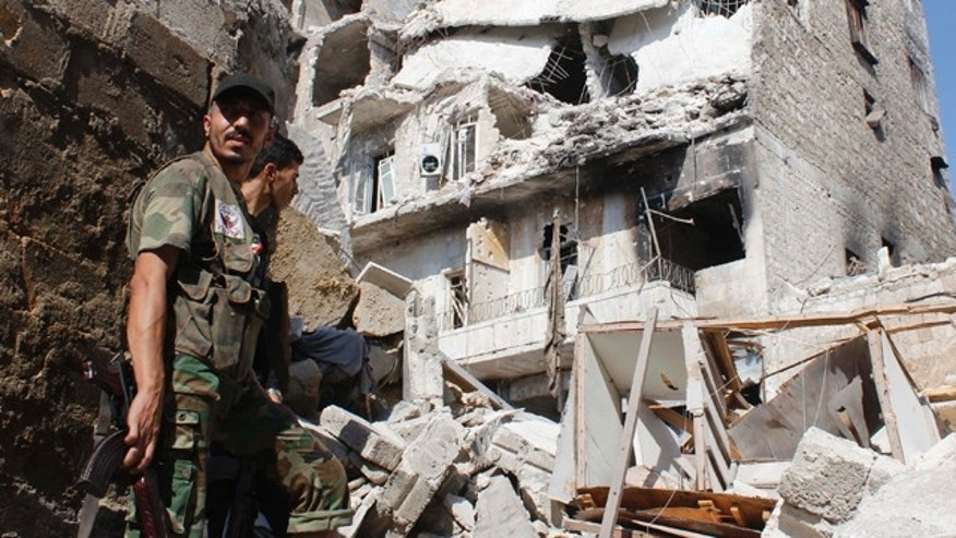 Sept. 2, 2013: Free Syrian Army fighters stand in front of buildings damaged by what activists said was shelling by forces loyal to Syria's President Bashar al-Assad in the old city of Aleppo.