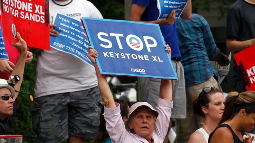 Protesters rally about the Keystone XL oil pipeline along  U.S. President Barack Obama's motorcade as he arrives at the Jefferson Hotel in Washington  July 11, 2013.