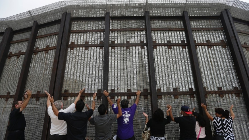 July 14, 2013: In this photo, pastors and others raise their arms on the San Diego side of a border fence during a cross-border Sunday religious service with others on the Tijuana, Mexico side of the fence.