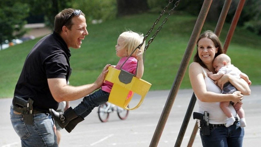 September 7, 2013: Brian Kuzawa pushes his two-year-old daughter Ashtyn on a swing as his wife Janae watches with younger brother Connor at Pleasant Street Park in Oberlin, Ohio. Both parents are carrying their handguns in the park, which is currently against Oberlin law, but allowed under Ohio law. (AP Photo/Joshua Gunter, The Plain Dealer)