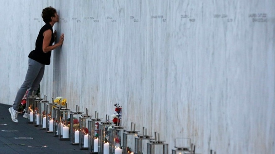 Sept. 10, 2013: A visitor kisses an name on the wall  containing the 40 names of the crew and passengers of Flight 93 at the Flight 93 National Memorial during a candlelight remembrance.