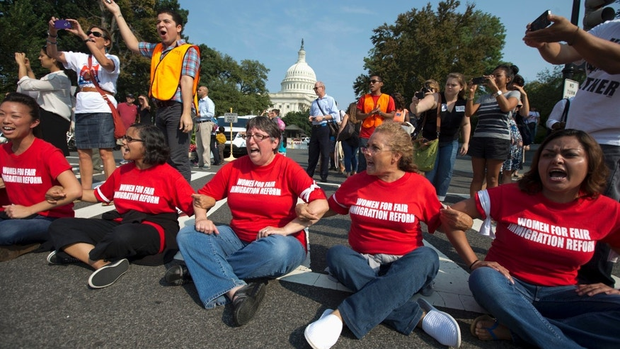 Women link arms outside the House of Representatives on Capitol Hill in Washington, Thursday, Sept. 12, 2013.