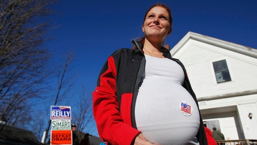 FILE: Nov. 6, 2012: A women with a voting sticker on her pregnant belly during the U.S. presidential election, outside of the old Town Hall in Bristol, N.H.