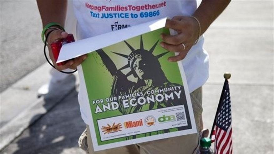 In this Aug. 16, 2013 photo, Jorge Galicia carries a poster in favor of immigration reform and carries a U.S. flag in his pocket in Miami. Immigration activists are trying to engage U.S. citizens in the immigration reform debate to obtain their support with visits to homes and small business. They are looking to mobilize the community to ask leadership from Republican congressmen at the House of Representatives to approve immigration reform that includes a path to citizenship. (AP Photo/J Pat Carter)