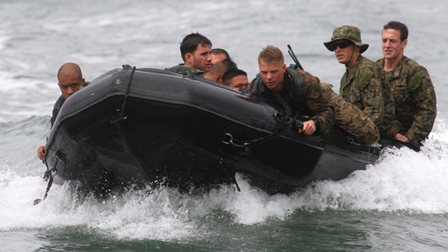 FILE: Sept. 20, 2013: U.S. Navy servicemen and Philippine marines in a rubber inflatable boat during joint military exercises at the Philippine Marines headquarters in Ternate, Cavite city, south of Manila.