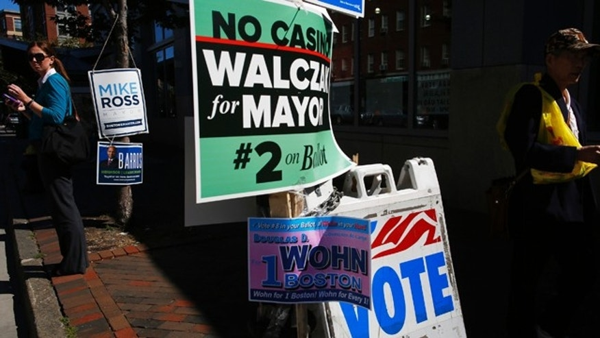 Sept. 24, 2013: Pedestrians stand and walk amidst campaign signs outside a polling station in Boston.