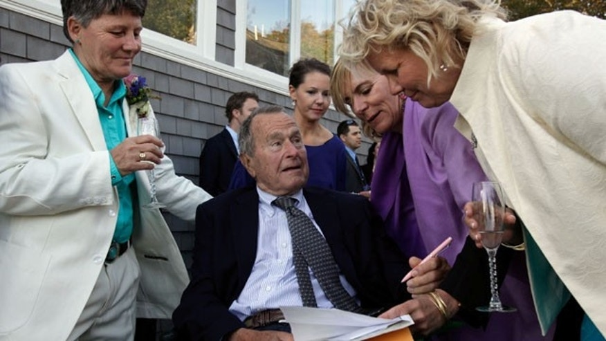 September 21, 2013:  Former President George H.W. Bush, seated center, prepares to sign the marriage license of longtime friends Helen Thorgalsen, right, and Bonnie Clement, left, in Kennebunkport, Maine, as officiant Nancy Sosa, third right, and Helen's daughter Lindsey, rear, look on. (AP Photo)