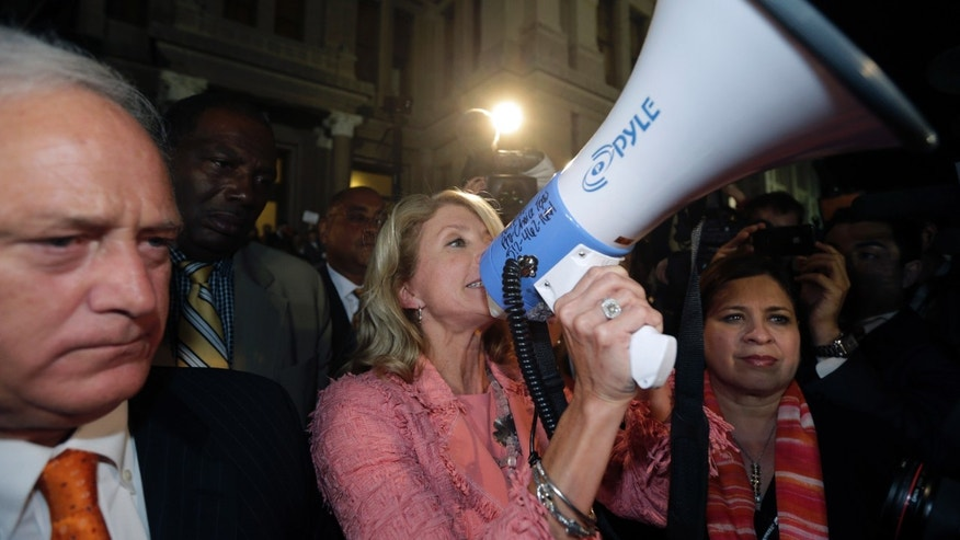 July 12, 2013: Sen. Wendy Davis, D-FortWorth, center, talks to supporters, using a megaphone outside the Texas Capitol after the Texas Senate passed an abortion bill in Austin, Texas.