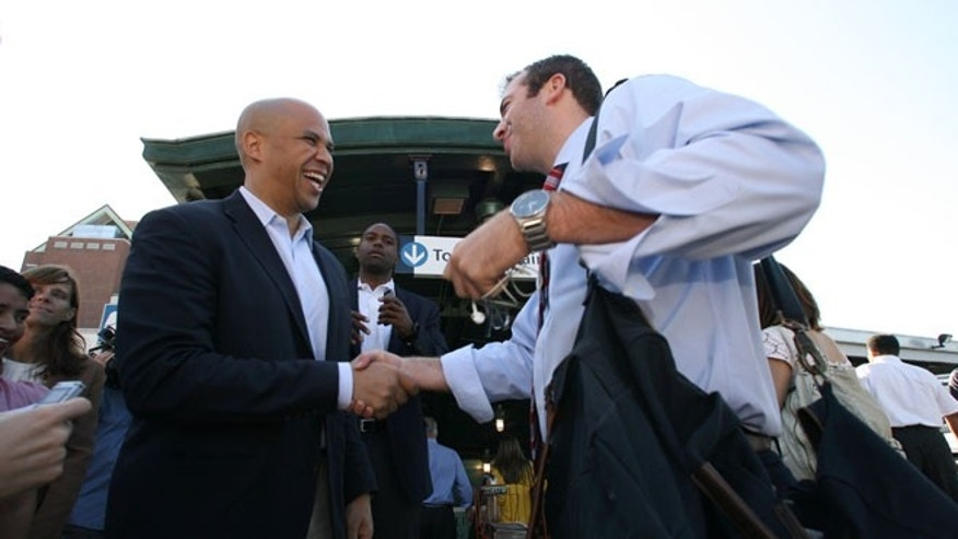 FILE: Aug. 14, 2013: U.S. Senate candidate, Newark Mayor Cory Booker, left, speaks with Sean Cleary, 24, of Hillsdale, N.J. on Wednesday,  in Hoboken, N.J.