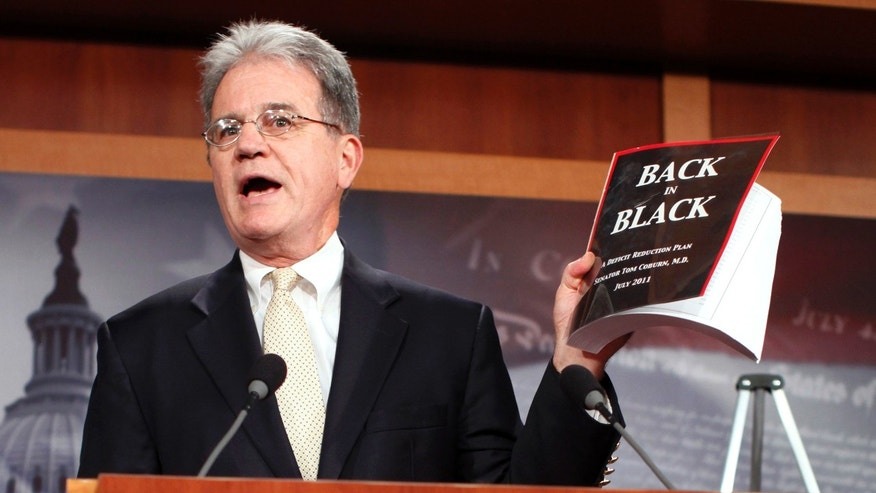 U.S. Senator Tom Coburn  holds up a copy of his deficit-reduction plan during a media availability in the Capitol in Washington July 18, 2011.