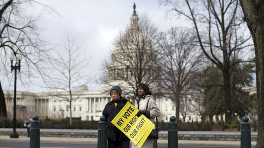 FILE - This Feb. 27, 2013, file photo shows people standing outside the Supreme Court in Washington before the start of a rally during arguments in the Shelby County, Ala., v. Holder case. (AP Photo)