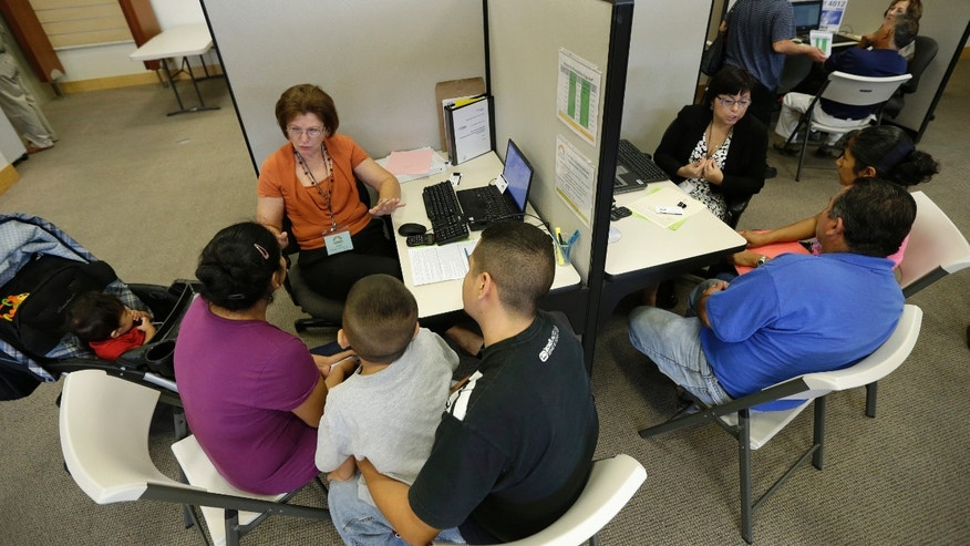 A volunteer counselor with Insure Central Texas explains health insurance options, Tuesday,  Oct. 1, 2013, in Austin, Texas.