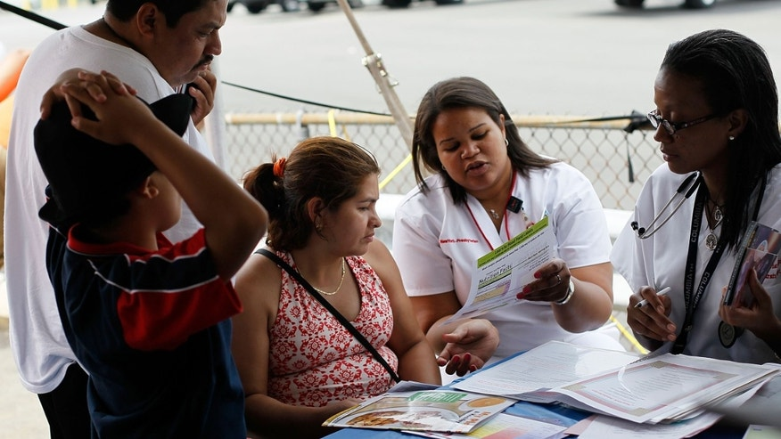 NEW YORK - JULY 20:  Edwidge Lafortune of New York Presbyterian Hospital (R, with paper) gives information on nutrition to workers and their families during a free health-screening clinic for New York bodega convenience store workers July 20, 2010 in the Bronx borough of New York. Nurses and technicians from  provided the free medical checks for the primarily-Hispanic bodega worker community, many of whom lack health insurance or regular medical care.  (Photo by Chris Hondros/Getty Images)