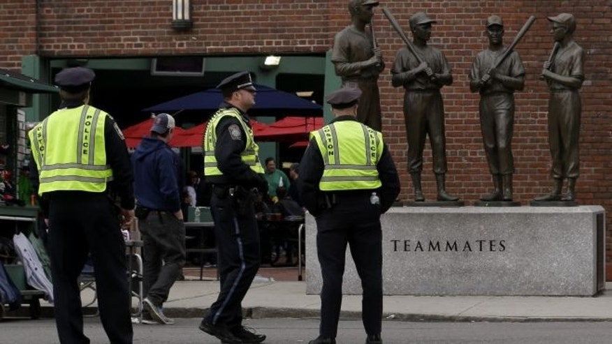 FILE: April 20, 2013: Police officers stand near statues of former Boston Red Sox greats, from left, Ted Williams, Bobby Doerr, Johnny Pesky and Dom DiMaggio during a baseball game in Boston.