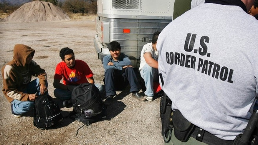 FILE - In this Jan. 19, 2007 file photo, the U.S. Border Patrol detains a large group of suspected immigrants at the Arizona-Mexico border in Sasabe, Ariz. A federal judge has barred use of a policy that allowed people who paid to be sneaked into the United States to be charged under Arizona's immigrant smuggling law as conspirators to the crime. U.S. District Judge Robert Broomfield's ruling said the interpretation of the 2005 state law conflicts with federal law. The ruling is the latest in a series of restrictions placed on Maricopa County Sheriff Joe Arpaio's immigration enforcement efforts. (AP Photo/Ross D. Franklin, File)