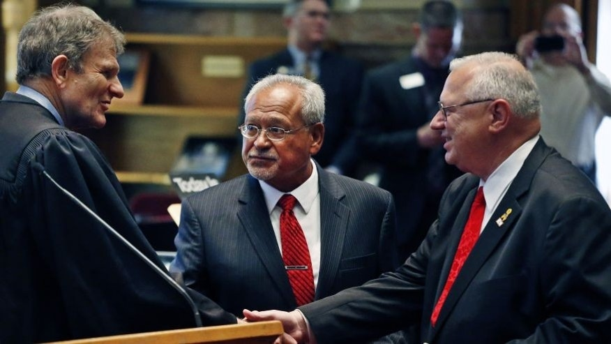 FILE: Oct. 3, 2013: Colorado Supreme Court Chief Justice Michael Bender, left, shakes hands with Republican state senator Bernie Herpin, as state senator George Rivera looks on after the two Republicans were sworn in, having defeated Colorado Democratic senators in a recall over new gun restrictions the previous month