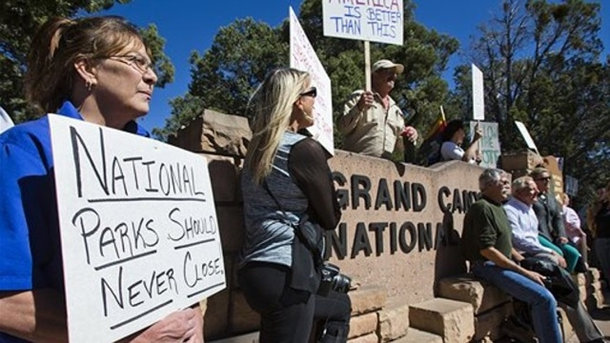 Oct. 8, 2013: Tammy Cox, left, a worker at a Holiday Inn in nearby Tusayan, Ariz., joins nearly 100 other protestors at a Welcome To The Grand Canyon sign outside the south entrance to the Grand Canyon.