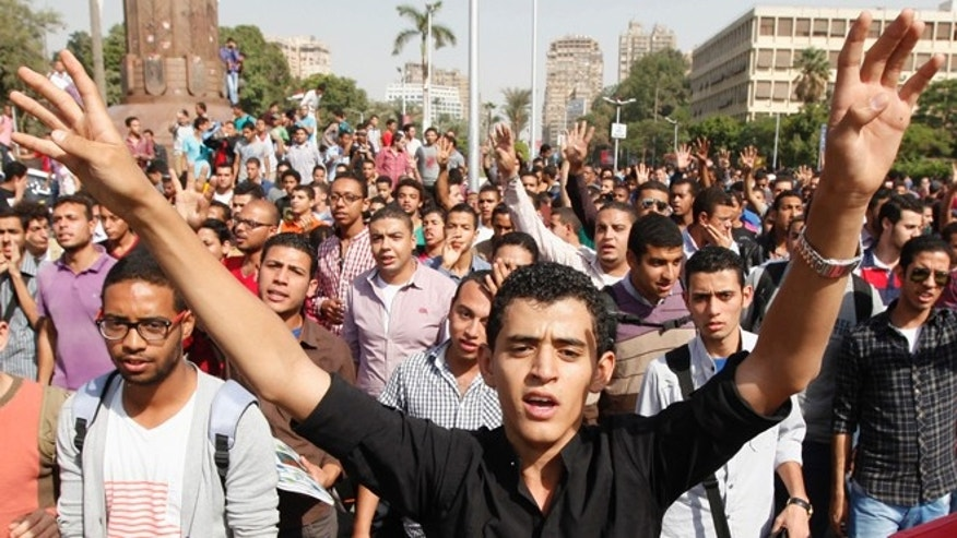 Oct. 8, 2013: Cairo university students and members of the Muslim Brotherhood shout slogans against the military in front of Cairo University in Cairo.