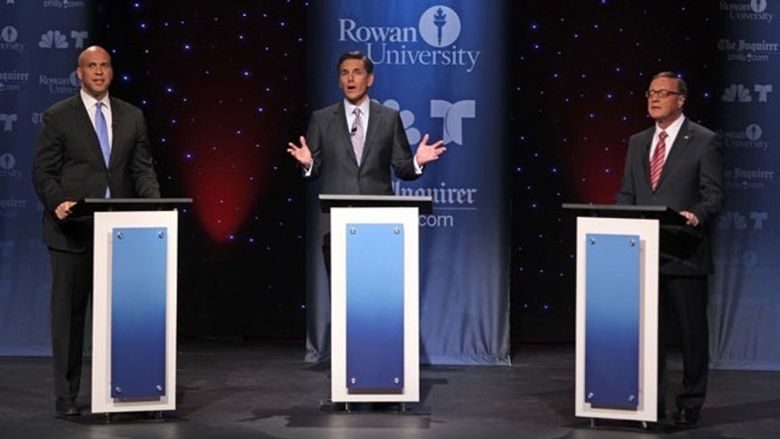 October 9, 2013: U.S. Senate candidates Cory Booker, left, and Steve Lonegan, right, appear in their second televised debate moderated by Jim Rosenfield, NBC 10, center, at Rowan University in Glassboro, N.J., Wednesday. (AP Photo/Philadelphia Inquirer)