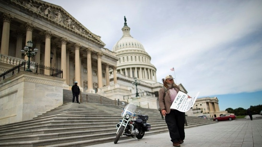 "Oct. 8, 2013: In this file photo, Rick Hohensee of Washington holds a ""Fire Congress"" sign near the House steps on Capitol Hill in Washington."