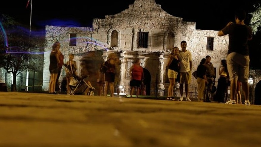 FILE: Aug. 1, 2013: Tourists make a late evening visit to the Alamo, in San Antonio. The Texas General Land Office, which took control of the Alamo in 2011, approved a gun rights rally for Saturday, Oct. 19, 2013, breaking with tradition that had kept demonstrations off the hallowed ground.