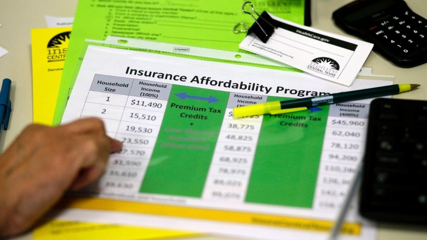 A volunteer counselor with Insure Central Texas uses a chart to help explain health insurance options in Austin, Texas.