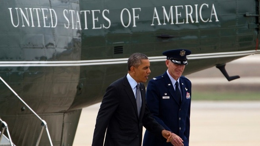 FILE: Oct. 30, 2013: President Obama walks with Col. David L. Almand, commander, 89th Airlift Wing, after getting off the Marine One helicopter at Andrews Air Force Base, Md.