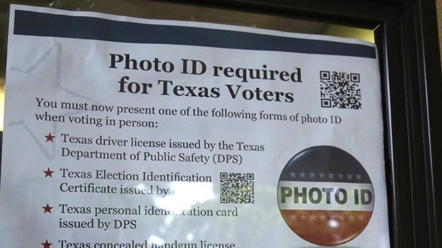 Tuesday, Nov. 5, 2013: A sign in a window tells of photo ID requirements for voting at a polling location in Richardson, Texas.