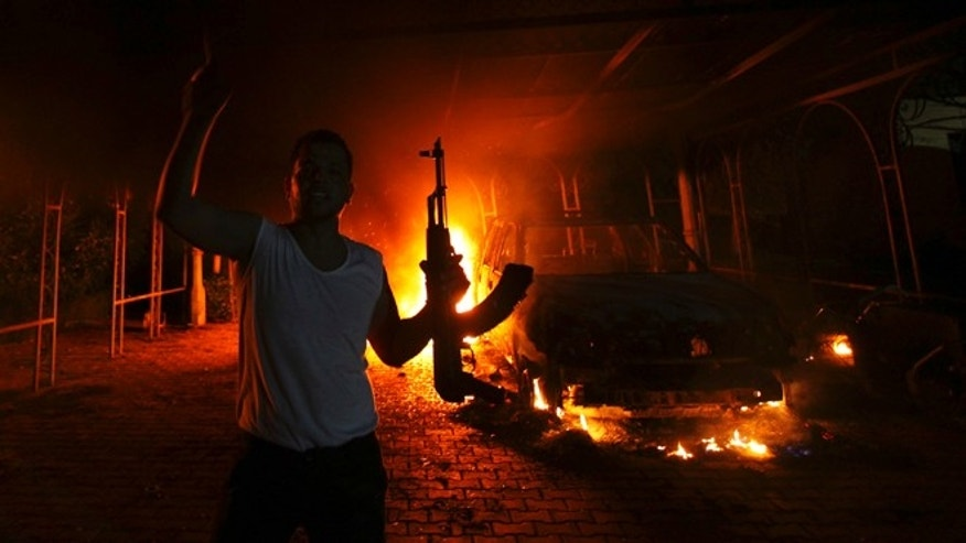 Sept. 11, 2012: A protester reacts as the U.S. Consulate in Benghazi is seen in flames during a terrorist attack which claimed the lives of four Americans.